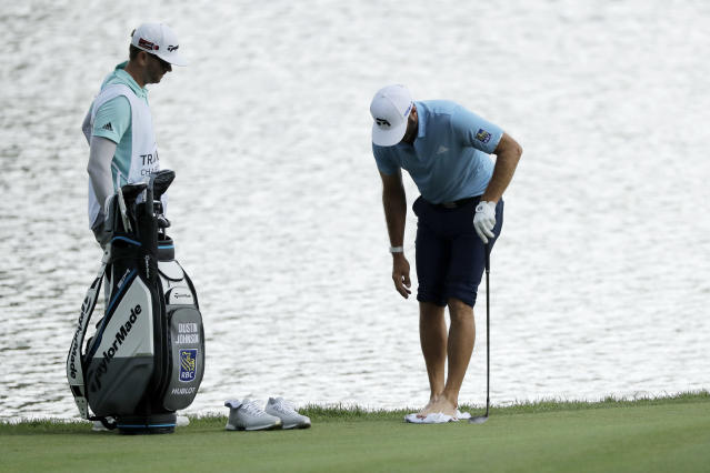 Dustin Johnson, right, cleans his feet after having to go in the pond to hit a ball on the rough on the 15th hole during the final round of the Travelers Championship golf tournament at TPC River Highlands, Sunday, June 28, 2020, in Cromwell, Conn. Johnson's brother and caddie, Austin Johnson, looks on. (AP Photo/Frank Franklin II)