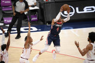 Washington Wizards guard Russell Westbrook (4) leaps up to pass the ball from between Cleveland Cavaliers center Jarrett Allen, right, forward Isaac Okoro, second from left, and guard Darius Garland, left, during the first half of an NBA basketball game Friday, May 14, 2021, in Washington. (AP Photo/Nick Wass)