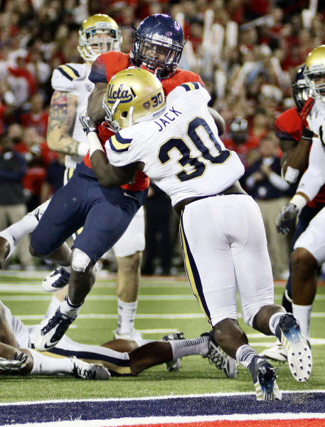 Arizona's Ka'Deem Carey, behind, drives to the endzone for a touchdown while UCLA's Myles Jack (30) holds on in the first half of an NCAA college football game, Saturday, Nov. 9, 2013 in Tucson, Ariz. (AP Photo/Wily Low)