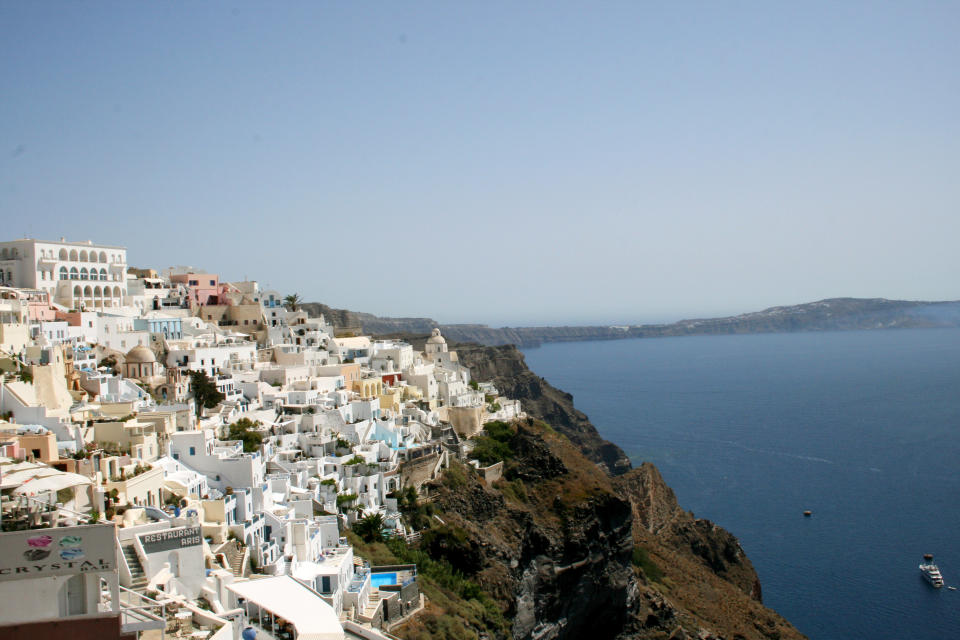 This July 2014 photo shows whitewashed homes stacked like sugar cubes on the seaside cliffs of Santorini, part of Greece's Cyclades island chain in the Aegean Sea. The Cyclades are known for panoramic waterfront views, black-sand beaches and dramatic sunsets. (AP Photo/Kristi Eaton)