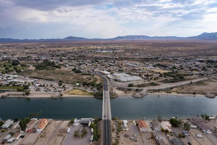 NEEDLES, CA - JUNE 23: The Colorado River flows along the Mojave desert town of Needles, top, on Wednesday, June 23, 2021 in Needles, CA. (Brian van der Brug / Los Angeles Times)