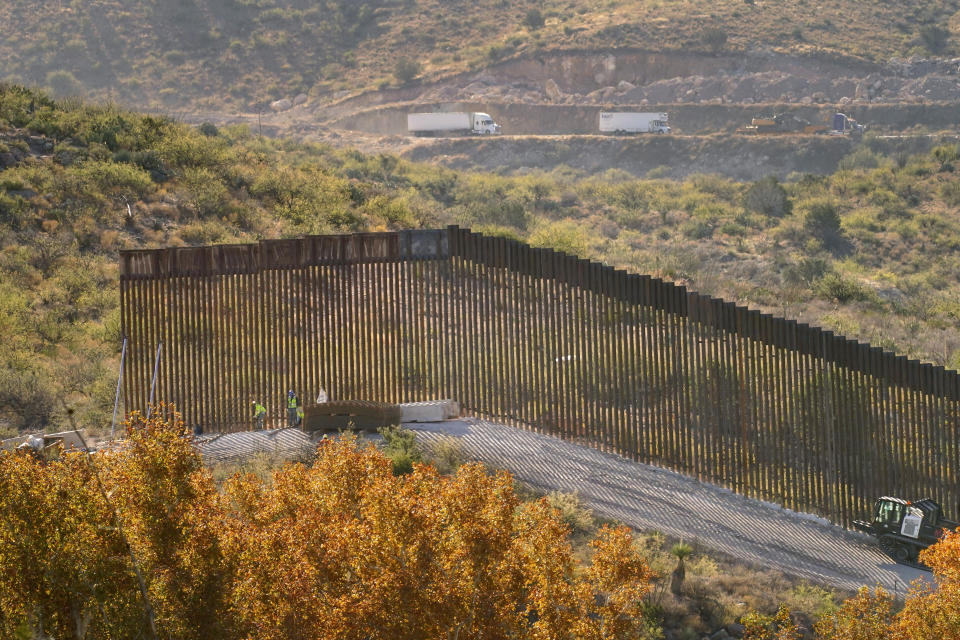 Trucks drive along Mexico's Route 2, top, as border wall construction continues along a cleared pathway, Wednesday, Dec. 9, 2020, in Guadalupe Canyon, Ariz. Crews have been dynamiting remote and rugged mountainsides in the southeast corner of Arizona, reshaping the landscape in an effort to build more border wall before President Trump's term ends in January. Construction of the border wall, mostly in government owned wildlife refuges and Indigenous territory, has led to environmental damage and the scarring of unique desert and mountain landscapes that conservationists fear could be irreversible. (AP Photo/Matt York)