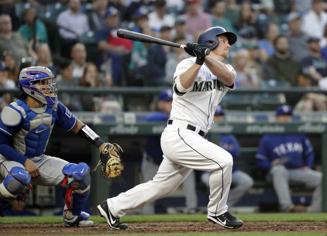 Seattle Mariners' Kyle Seager watches his three-run double in front of Texas Rangers catcher Robinson Chirinos during the third inning of a baseball game Tuesday, May 15, 2018, in Seattle. (AP Photo/Elaine Thompson)