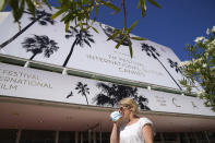 A member of the public walks past the Palais des Festival with a face mask during preparations for the 74th international film festival, Cannes, southern France, July 5, 2021. The Cannes film festival runs from July 6 - July 17. (AP Photo/ Vadim Ghirda)