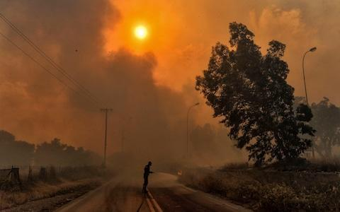 <span>A firefighter tries to extinguish hotspots during a wildfire in Kineta, near Athens</span> <span>Credit: AFP </span>