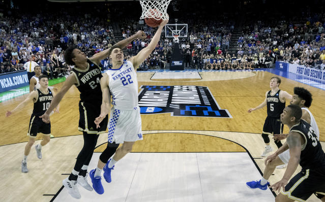 Kentucky's Reid Travis (22) goes up for a shot past Wofford's Keve Aluma, left, during the second half of a second-round game in the NCAA mens college basketball tournament in Jacksonville, Fla., Saturday, March 23, 2019. (AP Photo/Stephen B. Morton)