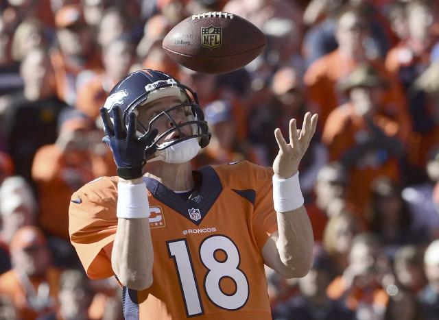 Denver Broncos quarterback Peyton Manning bobbles a snap before throwing a pass against the New England Patriots during the first quarter in the NFL's AFC Championship football game in Denver, January 19, 2014. REUTERS/Mark Leffingwell (UNITED STATES - Tags: SPORT FOOTBALL)