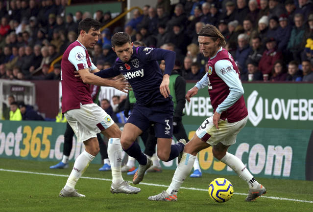 West Ham United's Aaron Cresswell, centre and Burnley's Jeff Hendrick, right, battle for the ball during the English Premier League soccer match between Burnley and West Ham United, at Turf Moor, in Burnley, England, Saturday, Nov. 9, 2019. (Ian Hodgson/PA via AP)