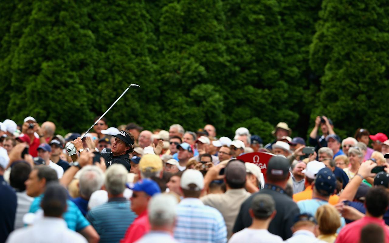 ROCHESTER, NY - AUGUST 06: A gallery of fans watches at Phil Mickelson of the United States hits a tee shot during a practice round prior to the start of the 95th PGA Championship at Oak Hill Country Club on August 6, 2013 in Rochester, New York. (Photo by Streeter Lecka/Getty Images)