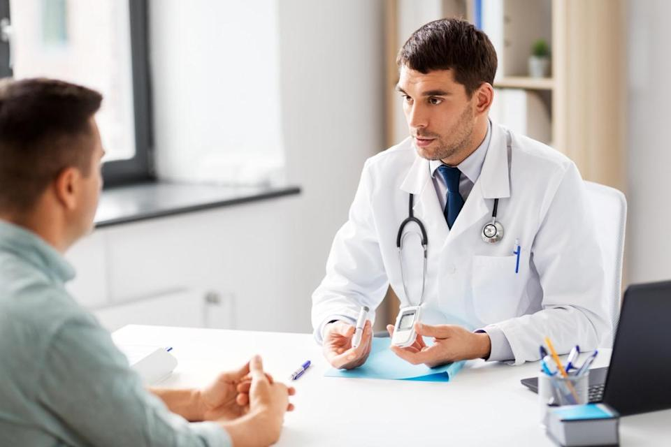 doctor with glucometer and insulin pen device talking to male patient at medical office in hospital