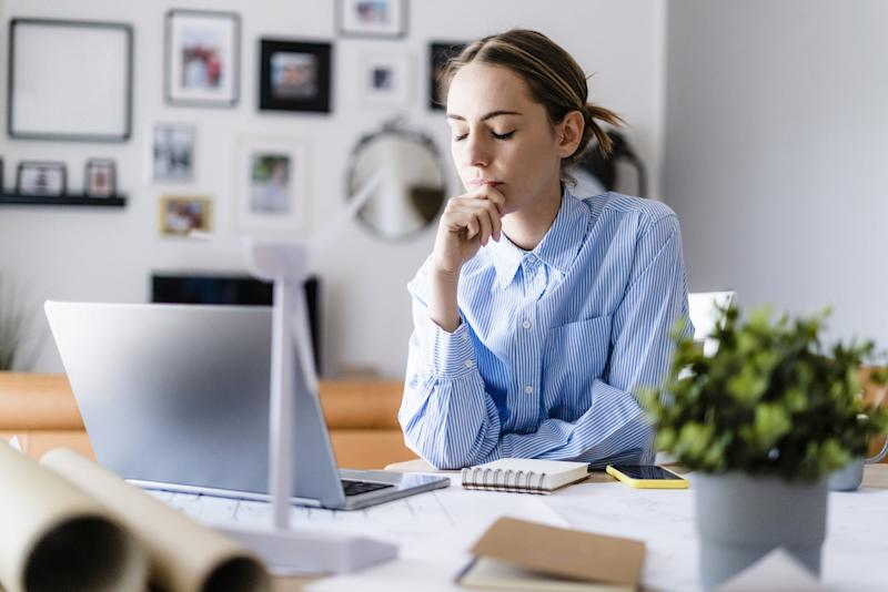 Woman with closed eyes in office with wind turbine model on table