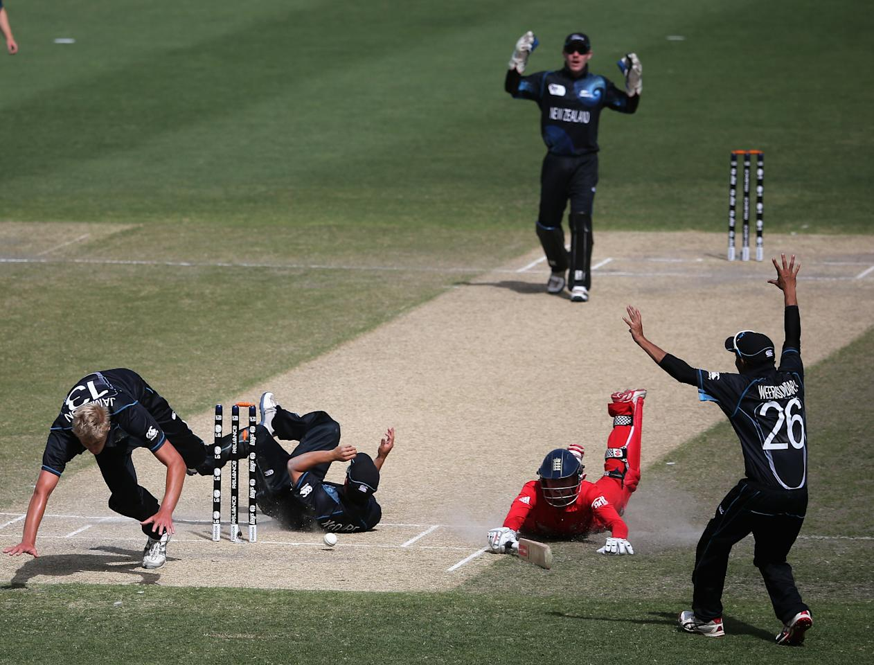 DUBAI, UNITED ARAB EMIRATES - FEBRUARY 18:  Players of New Zealand celebrate after dismissing Ed Barnard of England during the ICC U19 Cricket World Cup 2014 match between England and New Zealand at the Dubai Sports City Cricket Stadium on February 18, 2014 in Dubai, United Arab Emirates.  (Photo by Francois Nel - IDI/IDI via Getty Images)