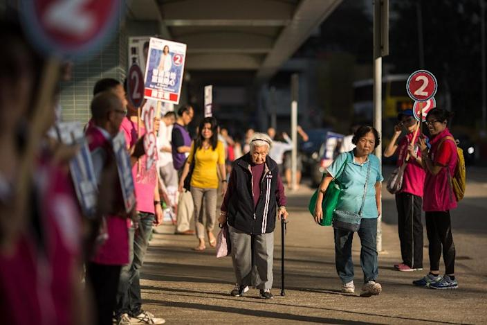 Pedestrians walk past a line of campaigners for election candidate Judy Chan of the New People's Party in the Southern district of Hong Kong on November 22, 2015 (AFP Photo/Anthony Wallace)