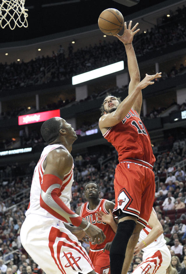 Chicago Bulls' Joakim Noah (13) shoots over Houston Rockets' Dwight Howard in the first half of an NBA basketball game on Wednesday, Dec. 18, 2013, in Houston. (AP Photo/Pat Sullivan)