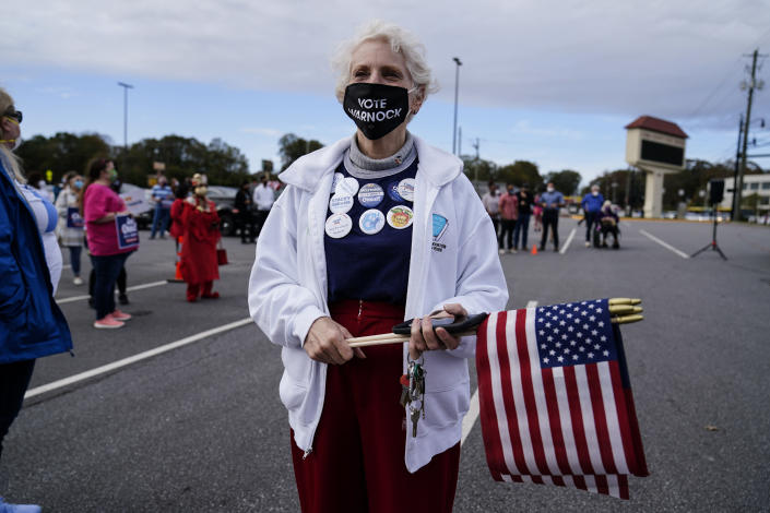 FILE - In this Nov. 15, 2020, file photo a supporter waits to hear Georgia Democratic candidate for U.S. Senate Jon Ossoff and Raphael Warnock speak during a rally in Marietta, Ga. (AP Photo/Brynn Anderson, File)