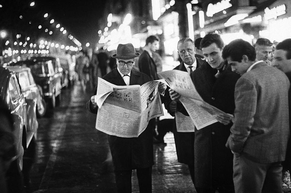Frenchmen reading newspaper reports of John F. Kennedy's assassination.