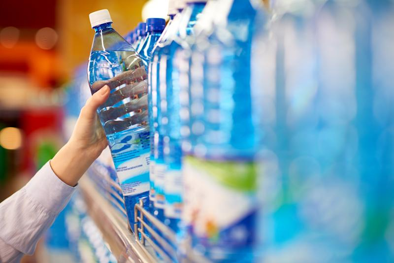 Pictured is a female hand taking bottle of mineral water from supermarket shelf.