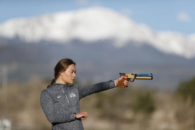 USA Olympic modern pentathlon team member Isabella Isaksen practices shooting at targets with Pike's Peak in the background in a park in Colorado Springs, Colo., Friday, April 24, 2020. (AP Photo/David Zalubowski)