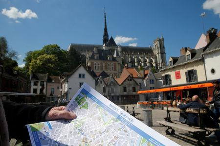 A tourist holds a map of the city of Amiens, France, May 16, 2019. Picture taken May 16, 2019.  REUTERS/Pascal Rossignol