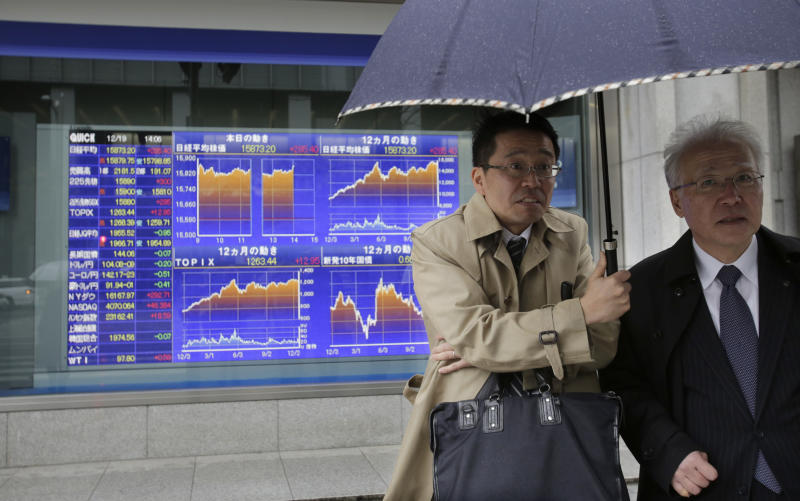 Two men share an umbrella as they wait to cross a street in front of an electronic stock board of a securities firm in Tokyo Thursday, Dec. 19, 2013. Asian markets were mixed Thursday after investors took the U.S. Federal Reserve's decision to trim its stimulus as a vote of confidence the American economy is strengthening. Japan's Nikkei 225 rose 271.42 points, or 1.74 percent to close at 15,859.22. (AP Photo/Shizuo Kambayashi)