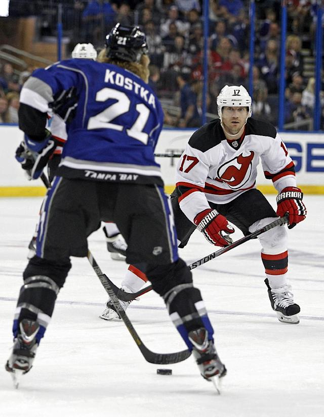 Tampa Bay Lightning defenseman Michael Kostka (21) defends the puck from New Jersey Devils right wing Michael Ryder (17) during the first period of an NHL hockey game Saturday, March 15, 2014, in Tampa, Fla. (AP Photo/Brian Blanco)
