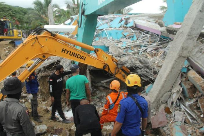 Rescuers use an excavator to dig through a damaged hospital building to search for survivors following an earthquake in Mamuju