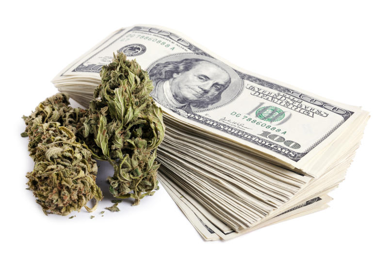 Dry Marijuana flower and a stack of cash money.