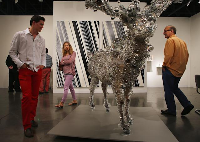 MIAMI BEACH, FL - DECEMBER 05: People look at a piece of art in the Scai The Bathhouse gallery as Art Basel opens at the Miami Beach Convention Center on December 5, 2012 in Miami Beach, Florida. The 11th edition of the art show runs from December 6 through the 9th. (Photo by Joe Raedle/Getty Images)