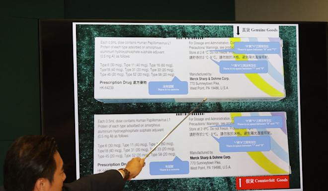 Kwan Kin-keung shows the differences between the boxes of what are believed to be genuine and fake vaccines. Photo: May Tse