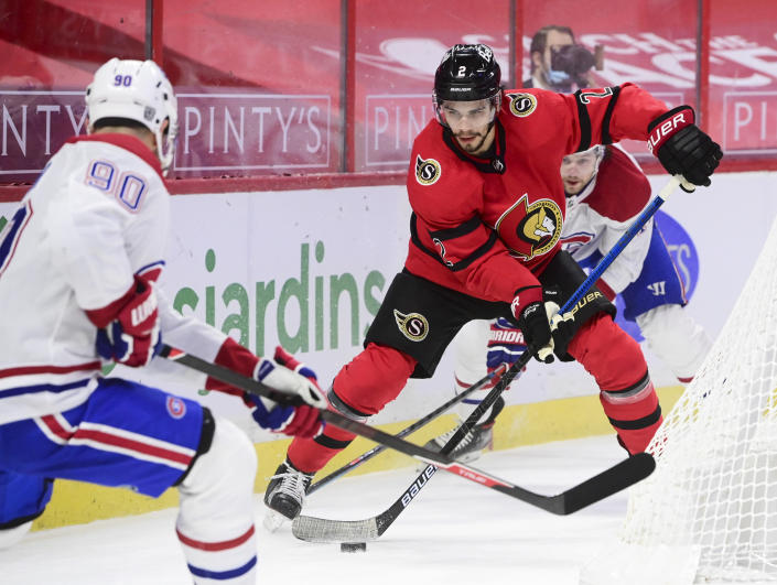 Ottawa Senators defenseman Artem Zub (2) looks to clear the puck while taking on the Montreal Canadiens left wing Tomas Tatar (90) during the first period of an NHL hockey game in Ottawa on Saturday, Feb. 6, 2021. (Sean Kilpatrick/The Canadian Press via AP)