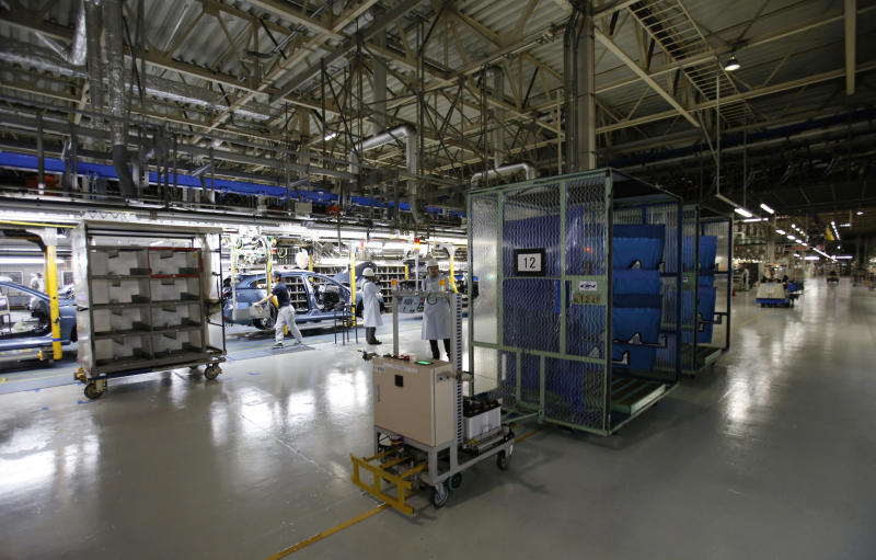 Auto parts are transported by automatic guided carts as Mazda employees, seen in the background left, work on the assembly line of the Mazda6 (Atenza) model at its plant in Hofu, Yamaguchi prefecture, southwestern Japan, Tuesday, Aug. 27, 2013. Mazda, the longtime also-ran of Japanese automakers, shows a new super-efficient plant that's rolling off vehicles at a stunning rate of one every 54 seconds. The plant is part of the reason why Mazda has managed to defy skeptics who've predicted fates ranging from bankruptcy to a buyout by Chinese interests. (AP Photo/Shizuo Kambayashi)
