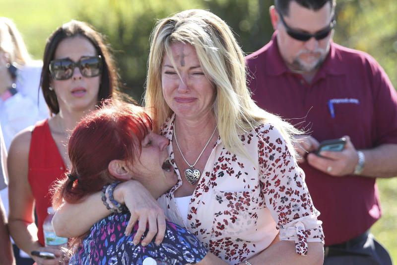 Parents wait for news after reports of a shooting at Marjory Stoneman Douglas High School in Parkland, Florida, on Wednesday. One woman had a cross on her forehead due to Ash Wednesday.