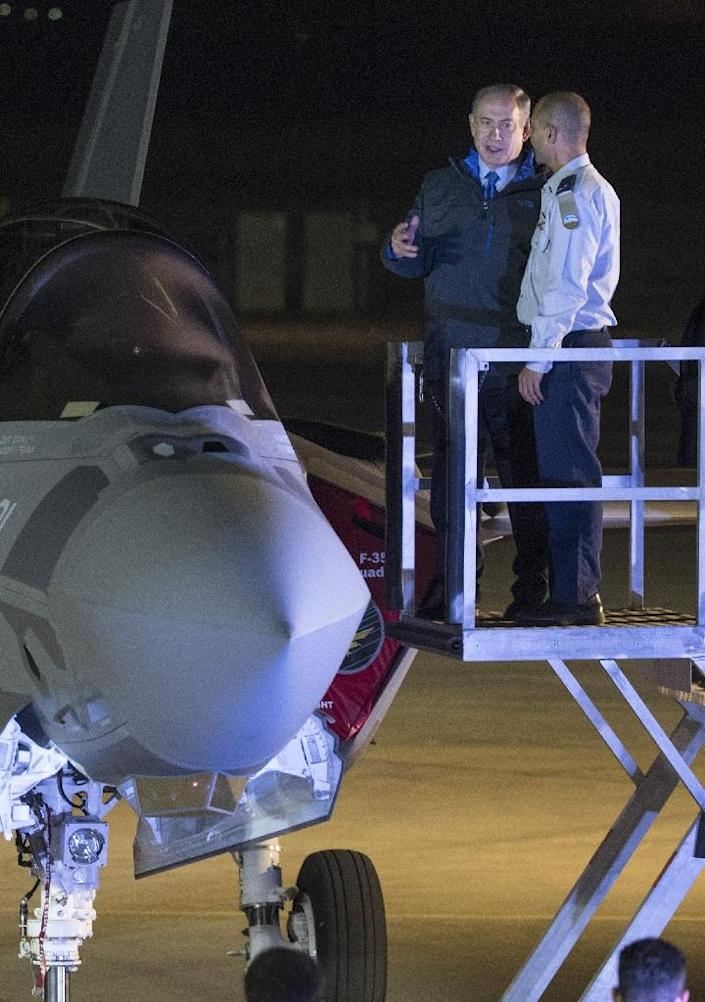 Israeli Prime Minister Benjamin Netanyahu (2ndR) looks at an F-35 stealth fighter jets with its pilot (AFP Photo/JACK GUEZ)