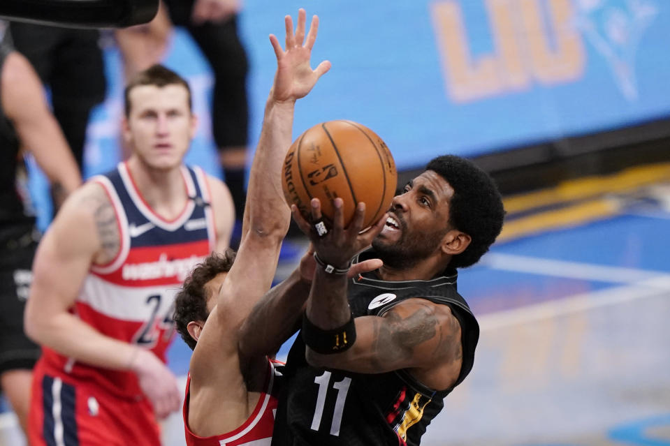 Washington Wizards guard Raul Neto defends against Brooklyn Nets guard Kyrie Irving (11) as Wizards forward Garrison Mathews (24) looks on during the first quarter of an NBA basketball game, Sunday, March 21, 2021, in New York. (AP Photo/Kathy Willens)