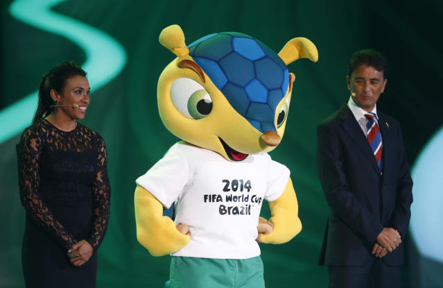 Mascot Fuleco is flanked by former Brazilian players Marta, left, and Bebeto during the draw ceremony for the 2014 soccer World Cup in Costa do Sauipe near Salvador, Brazil, Friday, Dec. 6, 2013. (AP Photo/Victor R. Caivano)
