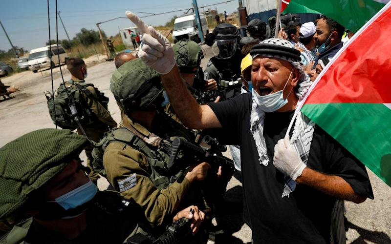 A demonstrator holding a Palestinian flag gestures in front of Israeli forces during a protest against Israel's plan to annex parts of the West Bank - Reuters