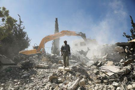 Palestinian Jihad Shawamrah stands on the ruins of his house that he demolished to not face the prospect of Israeli settlers moving in after he lost a land ownership case in Israeli courts, in the East Jerusalem neighbourhood of Beit Hanina
