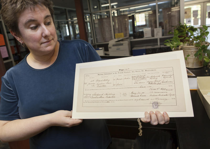 In this Oct. 2, 2013 photo, Marlboro College Librarian Emily Alling holds Rudyard and Caroline Kipling's marriage license, part of the College's Rudyard Kipling Collection, in Marlboro, Vt. The document is signed by the writer Henry James, who served as a witness. Kipling scholars from the United Kingdom and the U.S. will be at the college Monday and Tuesday, Oct. 7 and 8, 2013, for the first-ever meeting of the Kipling Society outside the U.K. (AP Photo/Matthew Cavanaugh)