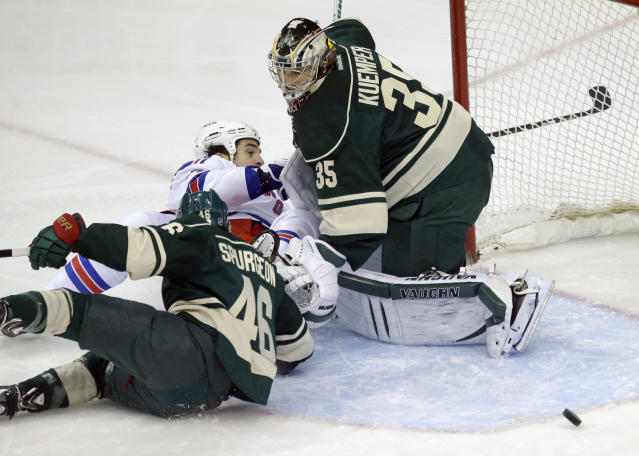 Minnesota Wild's Jared Spurgeon (46) and New York Rangers' Brian Boyle slide into Minnesota Wild goalie Darcy Kuemper, right, who deflects a shot by Boyle in the first period of an NHL hockey game on Thursday, March 13, 2014, in St. Paul, Minn. (AP Photo/Jim Mone)