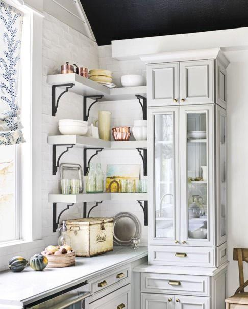 <p>The black brackets on these shelves make a bold, industrial statement in a white and gray kitchen. Mix materials for added interest (note the brass cabinet pulls and stainless steel appliances).</p>