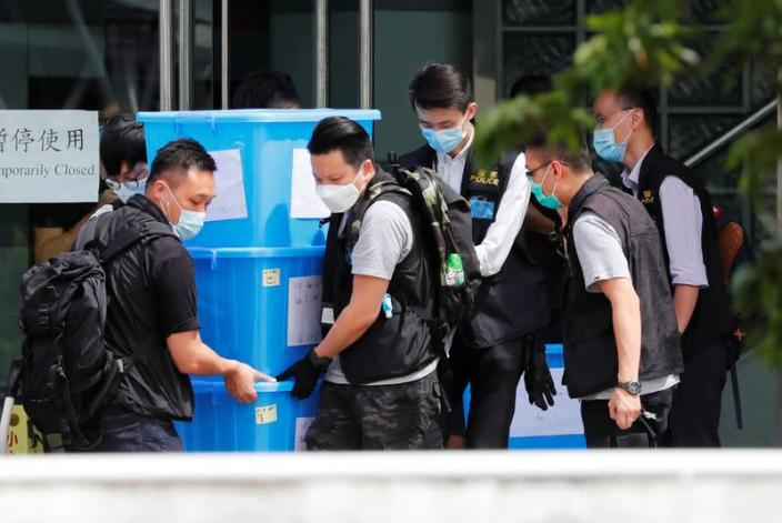 Police officers collect evidence from the headquarters of Apple Daily and Next Media after media mogul Jimmy Lai Chee-ying, founder of Apple Daily was detained by the national security unit in Hong Kong