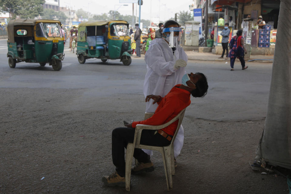 A health worker takes a nasal swab sample of a man to test for COVID-19 in Ahmedabad, India, Monday, Jan. 4, 2021. India on Sunday authorized two COVID-19 vaccines, paving the way for a huge inoculation program to stem the coronavirus pandemic in the world's second most populous country. (AP Photo/Ajit Solanki)