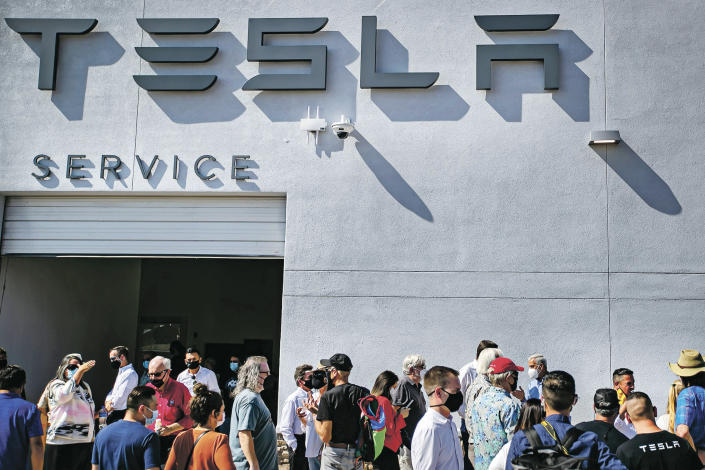 Tesla owners, Tesla employees and local political leaders gather at the service bay doors during an event on Sept. 9, 2021, to celebrate a partnership between Tesla and the Nambé Pueblo after the electric car company repurposed a defunct casino into a sales, service and delivery center near Santa Fe, N.M. Tesla has opened a store on tribal land in New Mexico, sidestepping car dealership laws that prohibit car companies from selling directly to customers. (Jim Weber/Santa Fe New Mexican via AP)