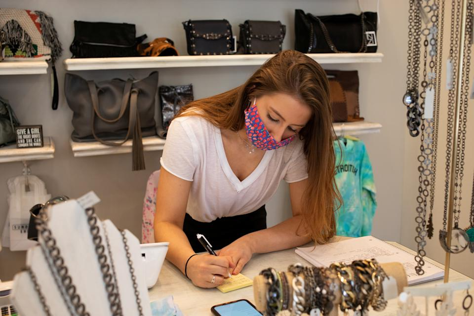 An employee wearing a protective mask writes down details to ship an order to a customer at Sundance Shoes amid an outbreak of the coronavirus disease (COVID-19) in Birmingham, Michigan, U.S., May 27, 2020. REUTERS/Emily Elconin