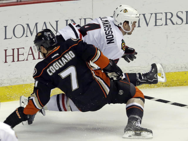 Chicago Blackhawks defenseman Niklas Hjalmarsson (4), of Sweden, and Anaheim Ducks center Andrew Cogliano (7) tangle during the second period of an NHL hockey game in Anaheim, Calif., Wednesday, Feb. 5, 2014. (AP Photo/Reed Saxon)
