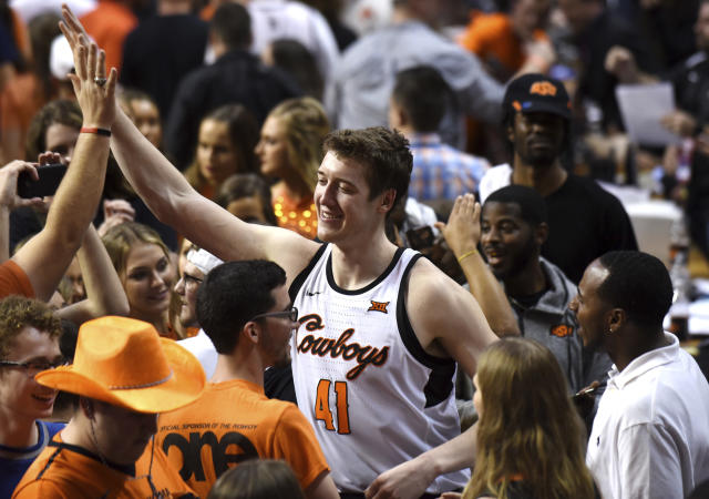 Oklahoma State forward Mitchell Solomon celebrates with fans that stormed the court following an NCAA college basketball game against Kansas in Stillwater, Okla., Saturday, March 3, 2018. (AP Photo/Brody Schmidt)