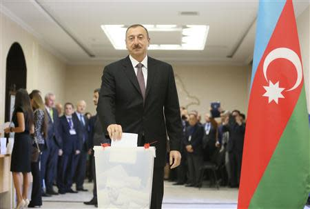 Azeri President Ilham Aliyev casts his vote in the presidential election at a polling station in Baku