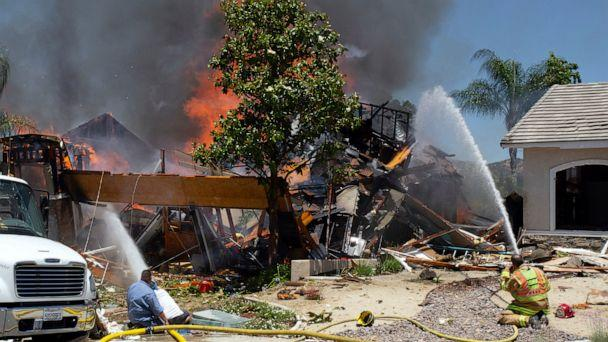 PHOTO: A firefighter and civilians train fire hoses on a burning home after an explosion and fire destroyed the home in Murrieta, Calif., sending up thick flames and closing several streets. (Andrew Foulk/AP)