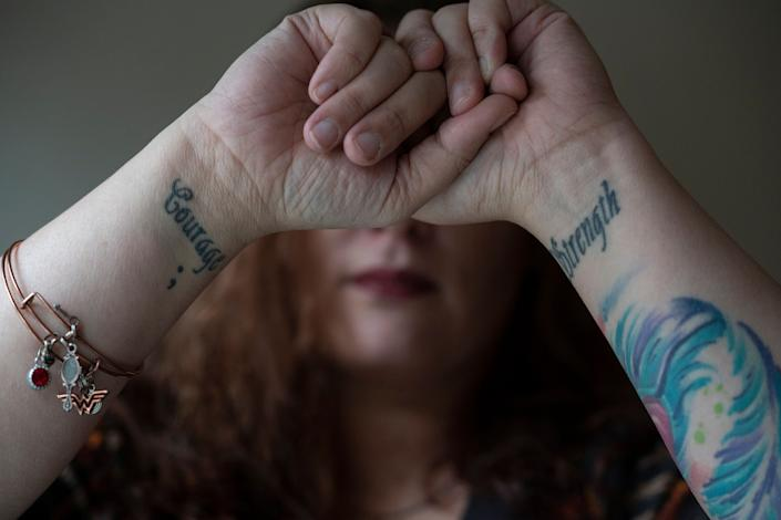 "Before leaving her ex-husband she got tattoos on her wrists with the words ""Strength"" and ""Courage"" to remind herself, she said, that she had both inside of her.  (Photo: Melissa Lyttle for HuffPost)"
