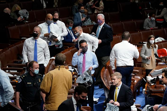 Lawmakers put on masks on the floor of the House of Representatives as a mob enters the U.S. Capitol on Jan 6.